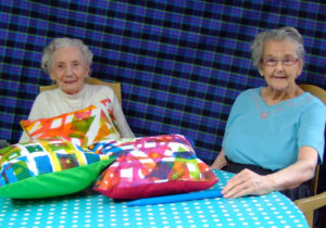 two friends feeling proud of their cushions, art in care homes