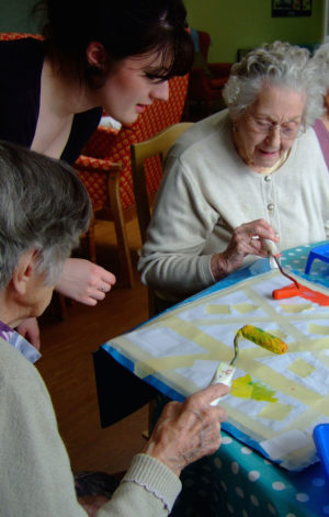 rolling colour over the taped fabric, art in care homes