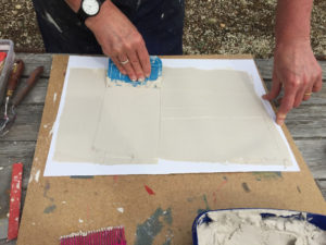 Smoothing a thin layer of cement with a plastic scraper