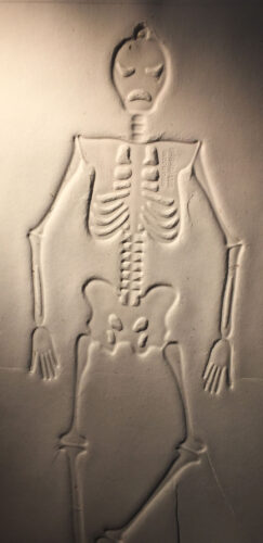 a toy skeleton embossed on paper