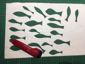 cutting fish from textured wallpaper