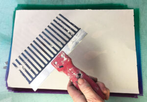 dragging the comb across the back of the paper